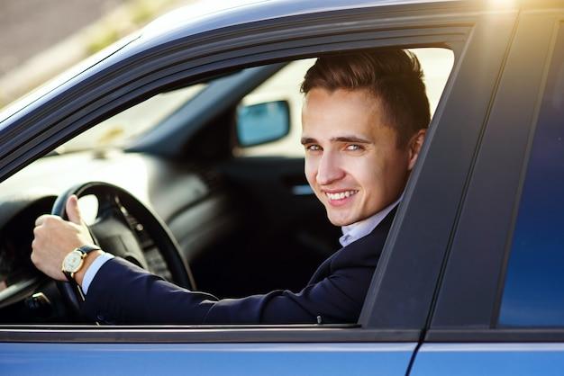 Atrakcyjny przystojny uśmiechnięty mężczyzna w garniturze jazdy drogim samochodem