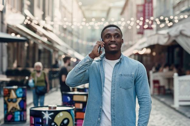 Atrakcyjny, radosny afroamerykanin ze stylową brodą prowadzi rozmowę telefoniczną podczas chodzenia po