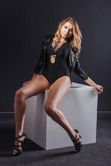 Atrakcyjny seksowny żeński tancerz siedzi na białym sześcianu czerni