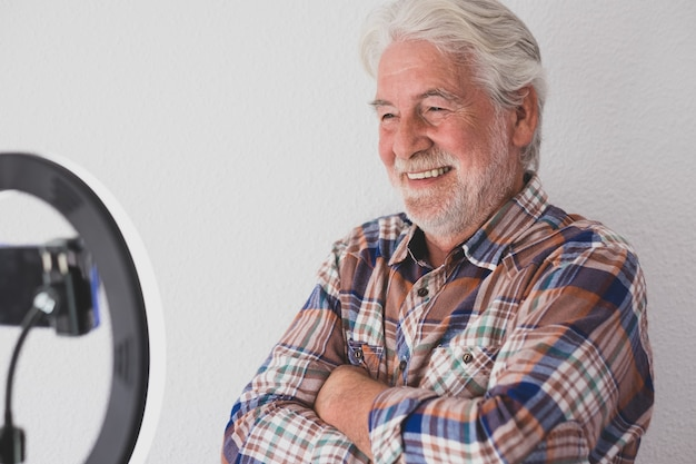 Atrakcyjny senior influencer w wideokonferencji online - białe tło