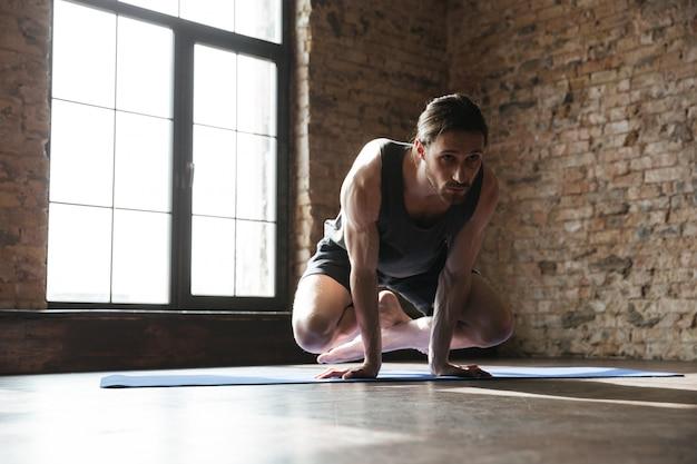 Atrakcyjny silny sportowiec na siłowni wykonuje ćwiczenia jogi