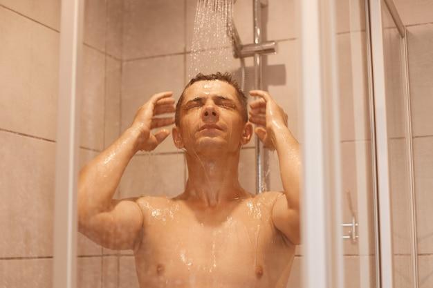 Atrakcyjny spokojny młody człowiek pod prysznicem, stojąc pod spadającymi kroplami wody, myjąc włosy, pozując nago, mając zamknięte oczy, odświeżenie po ciężkim dniu pracy.