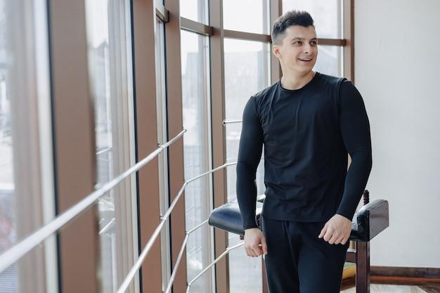 Atrakcyjny sportowy facet przy oknie. sportowiec pozowanie w pobliżu przestronnych okien. siłownia i sport.