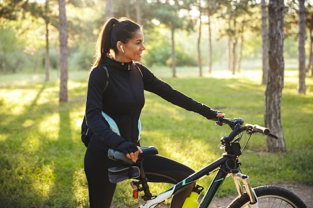 Atrakcyjny sprawny sportsmenka z rowerem w parku