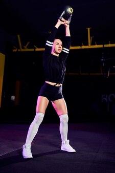 Atrakcyjny sprawny średnim wieku kobieta lekkoatletka wykonując huśtawka dzwon czajnik w siłowni cross fit