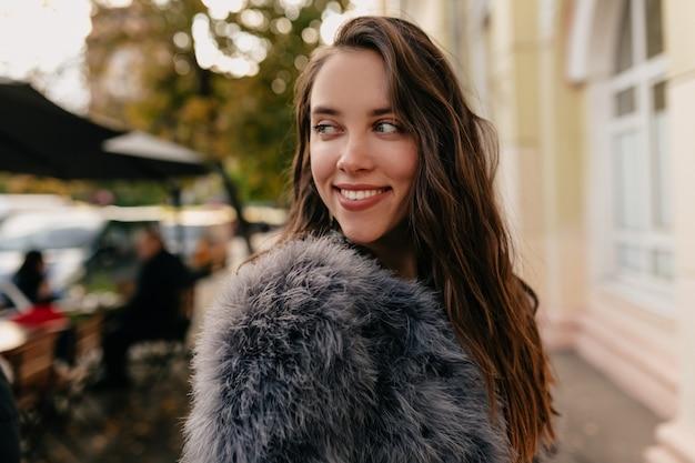 Atrakcyjny stylowy kaukaski dziewczyna w futrze, patrząc od hotelu i uśmiechając się na tle miasta.