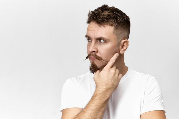 Atrakcyjny, stylowy, młody brodaty facet z wąsami myśli nad czymś, trzymając dłoń na twarzy, pozując na tle pustej ściany studia z miejscem na kopię informacji reklamowych