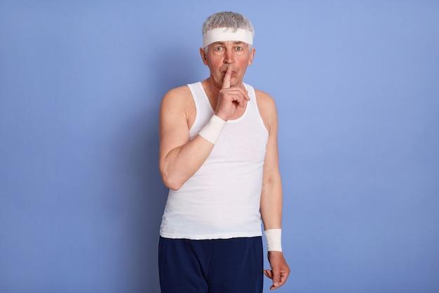 Atrakcyjny stylowy starszy mężczyzna ubrany w białą koszulkę bez rękawów, wykonujący gest wyciszenia, trzymając palec wskazujący na ustach, prosząc o zachowanie sekretu, pozując.