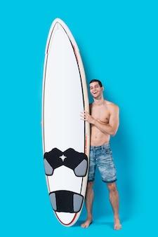 Atrakcyjny surfingowiec trzyma deskę surfingową