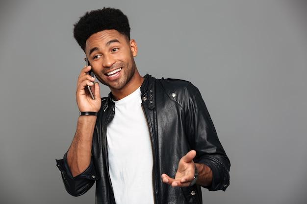 Atrakcyjny szczęśliwy afrykański facet ze stylową fryzurą rozmawia przez telefon, patrząc na bok