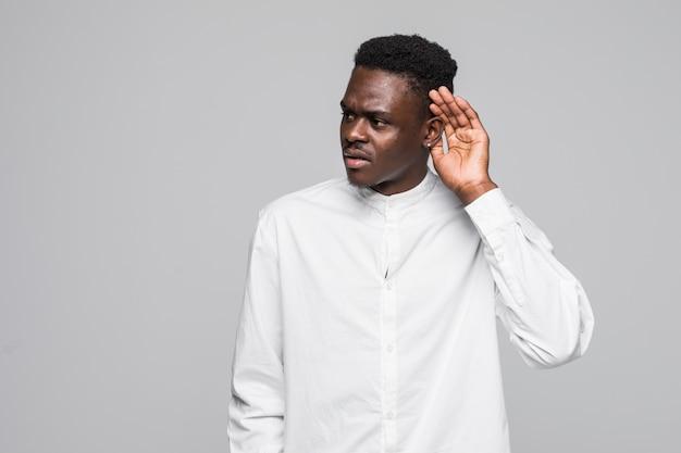 Atrakcyjny szczęśliwy ciemnooki afro-amerykański mężczyzna uśmiecha się i wyciąga rękę do ucha i pokazuje, że nie słyszy na białym tle szarym tle