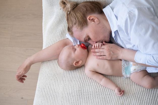 Atrakcyjny szczęśliwy dorosły pocałunek matki leżącej z małym chłopcem. sen.