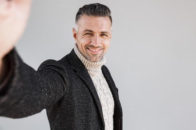 Atrakcyjny, szczęśliwy mężczyzna w płaszczu, stojący na białym tle nad szarą ścianą, robiący selfie