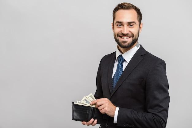 Atrakcyjny szczęśliwy młody biznesmen ubrany w garnitur stojący na białym tle nad szarą ścianą, pokazujący portfel pełen banknotów pieniędzy