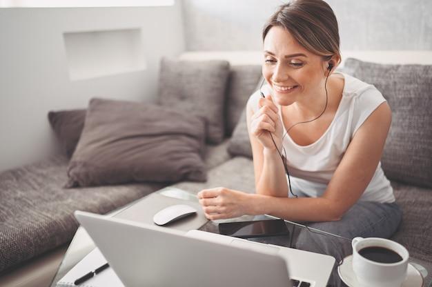 Atrakcyjny szczęśliwy młody student studiuje online w domu, przy użyciu komputera przenośnego, słuchawek, czatu wideo, macha. praca zdalna, kształcenie na odległość. konferencja wideo lub wirtualne wydarzenie na kwarantannie
