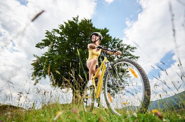 Atrakcyjny szczęśliwy rowerzysta dziewczyna jazda na żółty rower górski na trawiastym wzgórzu pod dużym drzewem, ciesząc się letni dzień w górach. aktywność na świeżym powietrzu, koncepcja stylu życia