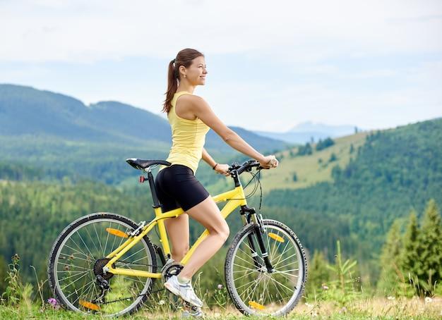 Atrakcyjny szczęśliwy rowerzysta kobieta jazda na żółtym rowerze górskim, ciesząc się letni dzień w górach. aktywność na świeżym powietrzu, koncepcja stylu życia