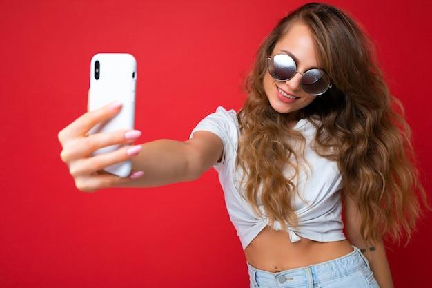 Atrakcyjny uroczy młoda uśmiechnięta szczęśliwa kobieta trzymając telefon komórkowy i przy użyciu telefonu komórkowego, biorąc selfie