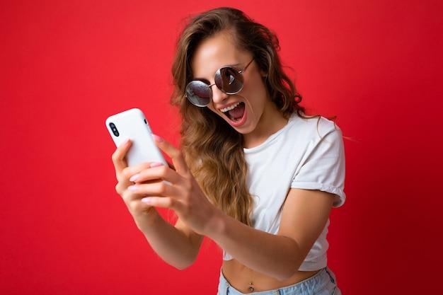 Atrakcyjny uroczy młody uśmiechnięta szczęśliwa kobieta trzymając telefon komórkowy i przy użyciu telefonu komórkowego, biorąc selfie na sobie stylowe ubrania