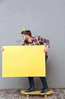 Atrakcyjny urodzinowy mężczyzna trzyma deskorolka na deskorolka