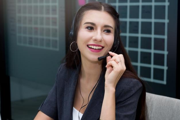 Atrakcyjny uśmiechnięty caucasian kobiety centrum telefoniczne z mikrofonu słuchawki oferuje klienta