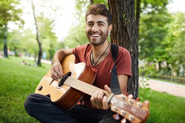Atrakcyjny uśmiechnięty facet siedzi w parku z gitarą, muzykiem grającym i śpiewa