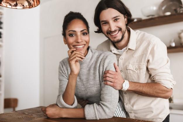 Atrakcyjny uśmiechnięty mężczyzna i całkiem afroamerykanin kobieta, opierając się radośnie na stole