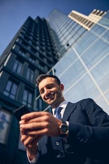 Atrakcyjny uśmiechnięty mężczyzna w oficjalnym stroju w pobliżu budynku wyglądający na szczęśliwego podczas oglądania czegoś w smartfonie