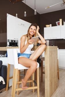 Atrakcyjny uśmiechnięty młodej dziewczyny obsiadanie przy kuchnią i słucha muzyka. patrząc na bok
