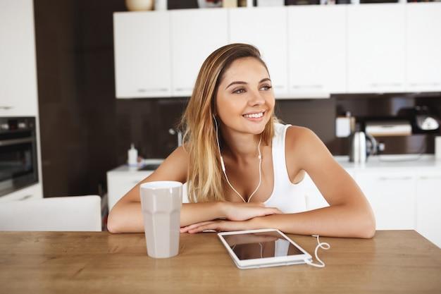 Atrakcyjny uśmiechnięty młodej dziewczyny obsiadanie przy obiadowym stołem i słucha muzyka na pastylce. patrząc na bok.