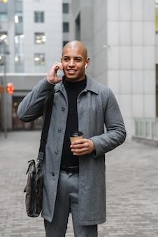 Atrakcyjny uśmiechnięty młody afrykanin w jesiennym płaszczu, stojąc na ulicy miasta, słuchając muzyki i pijąc kawę na wynos