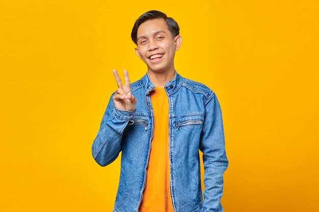 Atrakcyjny uśmiechnięty młody azjata robi znak pokoju ręką