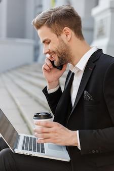 Atrakcyjny uśmiechnięty młody biznesmen w garniturze przy użyciu laptopa siedząc na ulicy miasta, rozmawiając przez telefon komórkowy