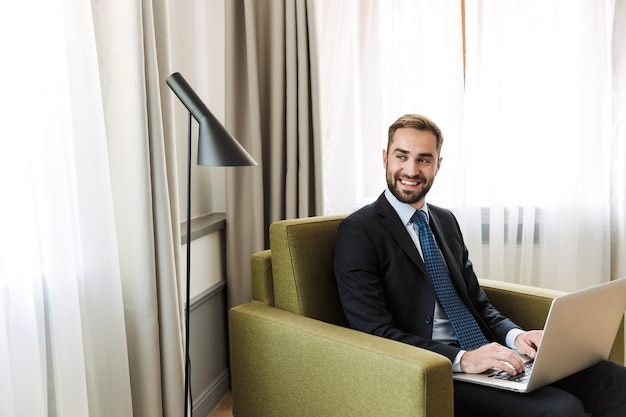 Atrakcyjny uśmiechnięty młody biznesmen w garniturze, siedzący na krześle w pokoju hotelowym, pracujący na laptopie