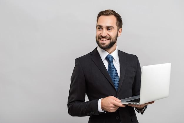 Atrakcyjny uśmiechnięty młody biznesmen w garniturze stojący na białym tle nad szarą ścianą, korzystający z laptopa