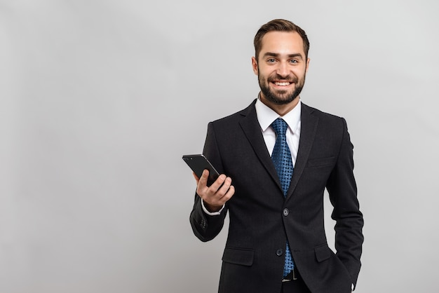 Atrakcyjny uśmiechnięty młody biznesmen w garniturze stojący na białym tle nad szarą ścianą, trzymający telefon komórkowy