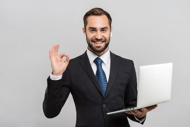 Atrakcyjny uśmiechnięty młody biznesmen w garniturze stojący na białym tle nad szarą ścianą, używający laptopa, ok gest