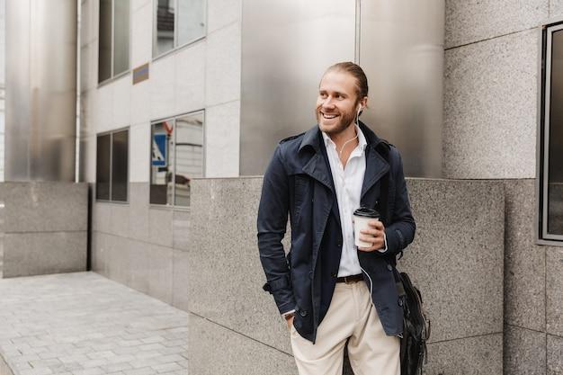 Atrakcyjny uśmiechnięty młody blond włosach mężczyzna w wizytowym stroju rozmawia przez słuchawki, trzymając filiżankę kawy na wynos, stojąc na zewnątrz na ulicy miasta