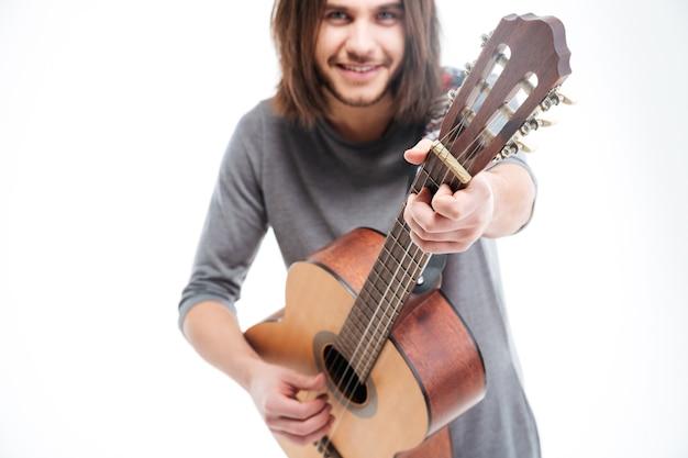 Atrakcyjny uśmiechnięty młody człowiek z długimi włosami grający na gitarze akustycznej na białym tle