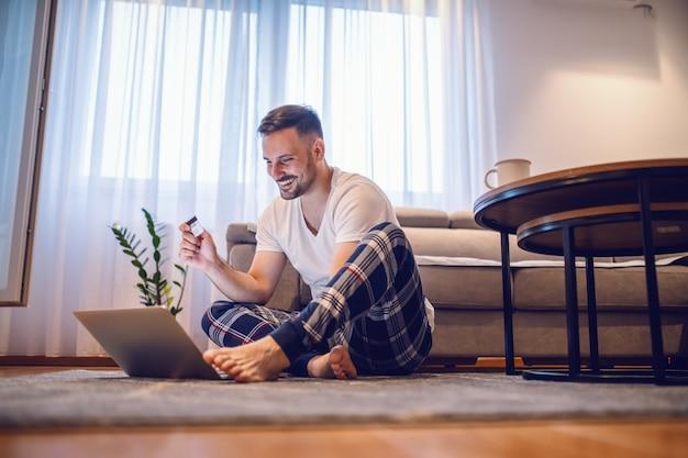 Atrakcyjny uśmiechnięty nieogolony kaukaski mężczyzna w piżamie siedzi na podłodze boso, trzyma kartę kredytową i korzysta z laptopa do płatności online.