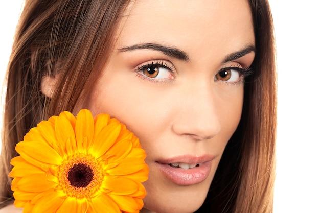 Atrakcyjny uśmiechnięty portret kobiety z kwiatem