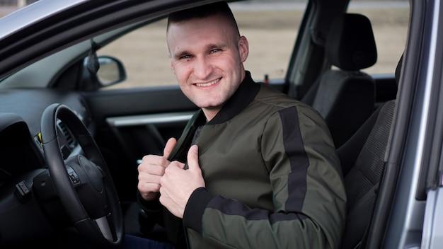 Atrakcyjny uśmiechnięty szczęśliwy młody człowiek w samochodzie