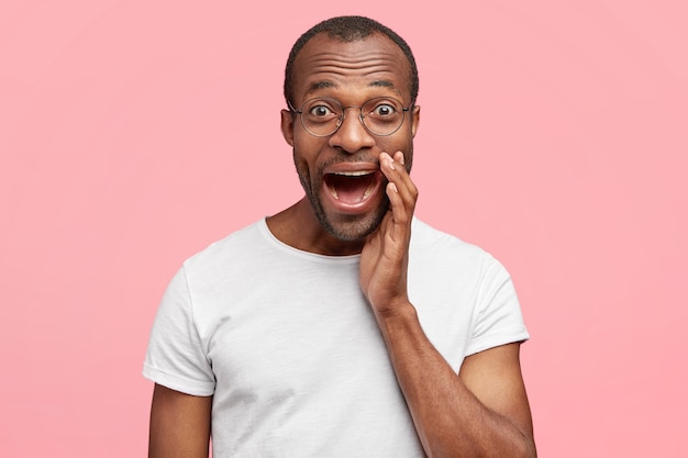 Atrakcyjny, uszczęśliwiony młody człowiek wyraża szczęśliwe emocje, cieszy się życiem, głośno wykrzykuje, ma szeroko otwarte usta, ubrany w białą koszulkę, stoi na różowej ścianie