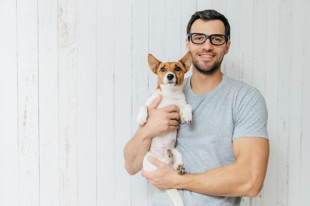 Atrakcyjny wesoły kaukaski mężczyzna w swobodnej koszulce, okularach, trzyma ulubionego zwierzaka