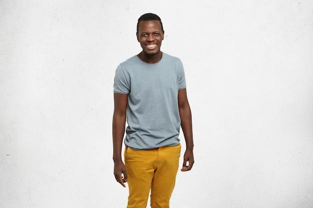 Atrakcyjny, wesoły młody ciemnoskóry student w szarym t-shircie i musztardowych dżinsach pozuje przy białej pustej ścianie, uśmiecha się radośnie, miło spędza czas w domu po wykładach na uczelni