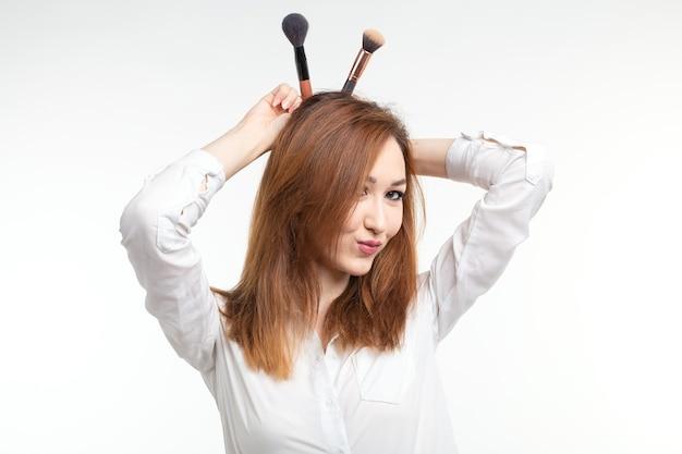 Atrakcyjny wizażysta lub koreański wizażysta wygłupiający się z pędzlami do makijażu na białej ścianie