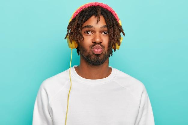 Atrakcyjny zabawny facet ma złożone usta, lubi ładne kawałki nowych słuchawek stereo, słucha muzyki w czasie wolnym, ubrany w zwykły strój, odizolowany na niebieskiej ścianie studia