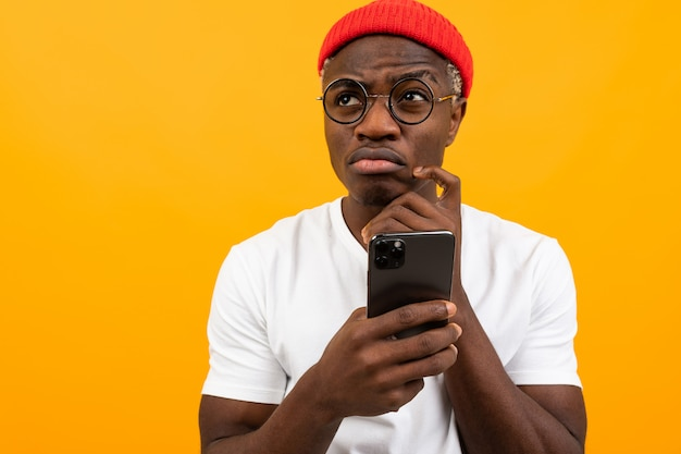 Atrakcyjny zadumany czarujący czarny człowiek w białej koszulce ze smartfonem w ręku na żółtym tle studio