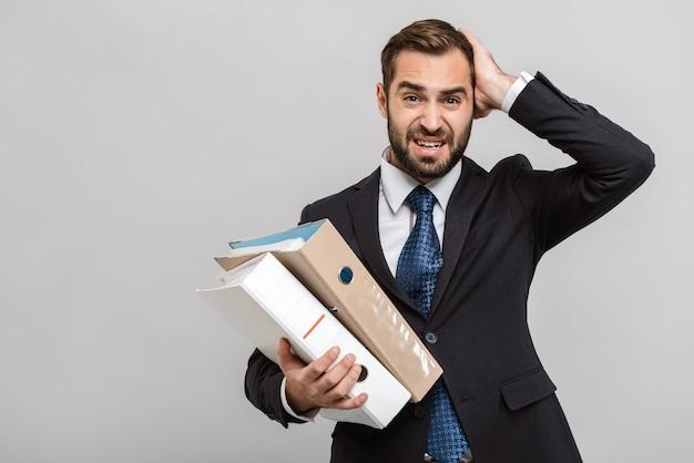 Atrakcyjny, zajęty młody biznesmen w garniturze stojący na białym tle nad szarą ścianą, trzymający foldery