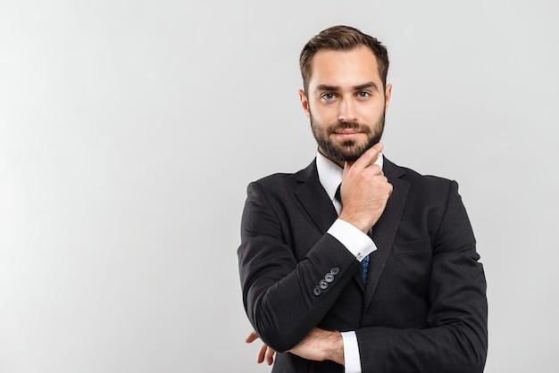 Atrakcyjny zamyślony młody biznesmen ubrany w garnitur stojący na białym tle nad szarą ścianą